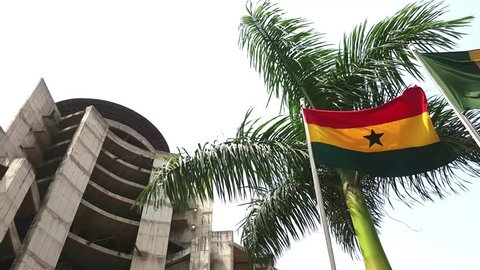 ACCRA, GHANA - MARCH 16, 2018 Flag of Ghana waving at wind with palm behind and building under construction on the left