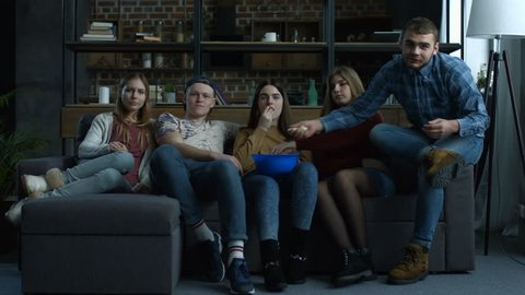 Group of cheerful teenage friends watching comedy movie on TV with popcorn and laughing while sitting on sofa at home. Excited casual friends relaxing and watching television in living room.