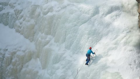 Ice Climbing Frozen Waterfall. Climbing Alpinism Winter.  Climber climbs on icy wall with wind and snow blowing. A man climbing a frozen waterfall. Climbing gear.