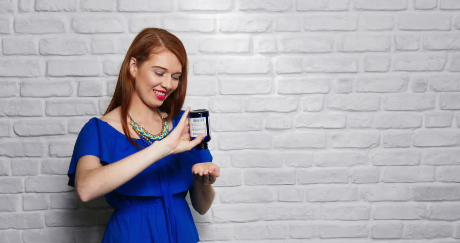 Young people, feelings and emotions. Portrait of happy white woman smiling. Redhead girl looking at camera and pouring pills into hand. Slow motion, copy space | Shutterstock HD Video #1008684178