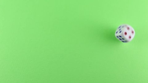 White plastic dice rolling on green background with number one