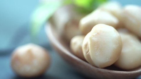 Close up of Roasted macadamias on stone table. Heathy food concept, selective focus for background and free space for text.