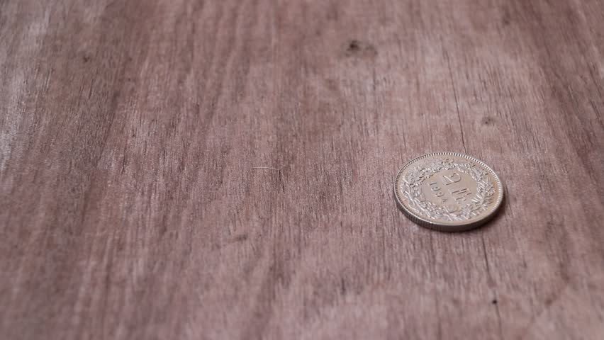 Spin of 2 Swiss Franc of Switzerland money on the wooden floor and stop in reverse of a coin with 1994. The concept of finance.   Shutterstock HD Video #1008716888