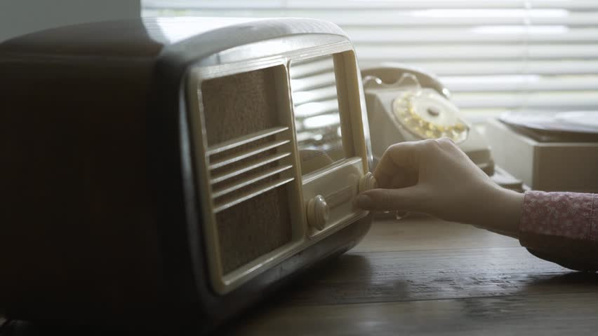 Woman tuning a vintage radio and searching for station frequencies, she is adjusting the knob