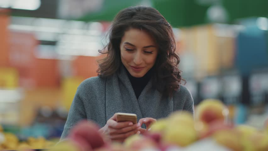 Woman doing grocery shopping at the supermarket and using phone look at camera smile
