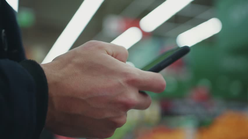 Close up man hand holding use phone in supermarket silhouette shopping  | Shutterstock HD Video #1008728978