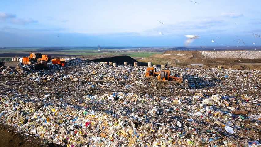 City Dump. The Bulldozer Moves Along the Landfill, Leveling the Garbage. Gulls Feeding on Food Waste Fly Over It. Aerial View | Shutterstock HD Video #1008733688