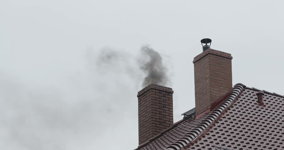 Residential house in a suburbs during cloudy day in cold winter is polluting the air with thick dark smoke. Smog coming out of the chimney.