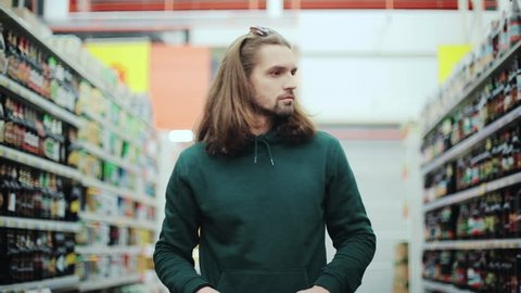 attractive man with long hair choosing bottle alcohol in the supermarket buy selection alcoholic sale handsome reading market people hand grocery looking male drink holding beer portrait slow motion