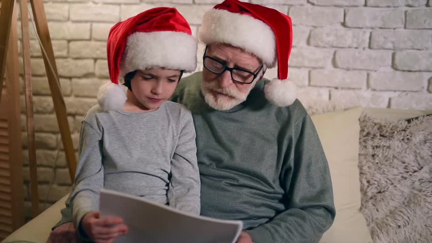 Gray haired grandfather and grandson are reading together in Santa Claus caps. Grandpa is reading book with grandson on eve of Christmas.