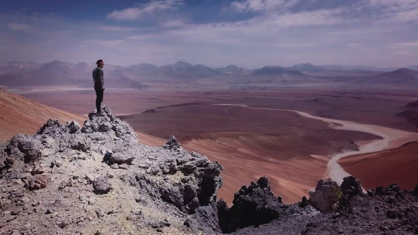 Male trail-runner on summit of the volcano Toco on Atacama desert, 4k. Aerial view of a man running down of a volcano peak.