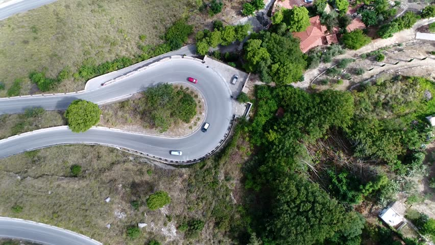 Aerial top down view of hairpin turn also called hairpin bend hairpin corner named for its resemblance to a hairpin bobby pin is bend in a road with a very acute inner angle vehicles driving over road