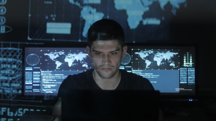 Young Man geek hacker overworking at computer and suffers from a headache in cyber security center filled with display screens. | Shutterstock HD Video #1008776738