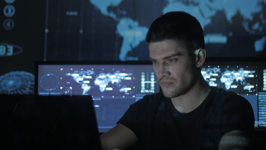 Young Man geek hacker overworking at computer and suffers from a headache in cyber security center filled with display screens. | Shutterstock HD Video #1008776768
