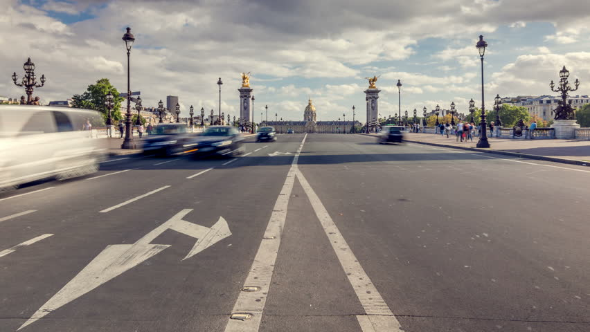 Car traffic on the Pont Alexandre III, famous arch bridge over the river Seine in Paris. Les Invalides building complex is in the background. Zoom in. | Shutterstock HD Video #1008779348
