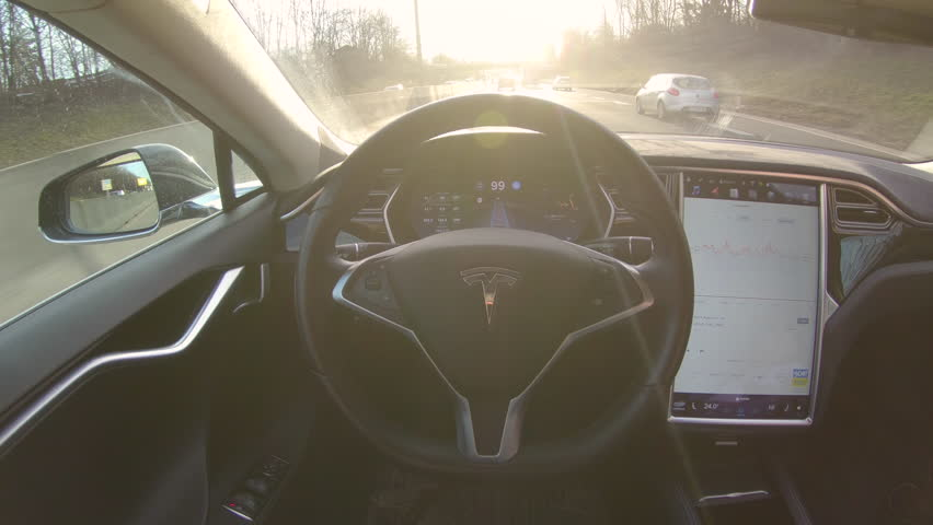 TESLA AUTONOMOUS CAR, MARCH 2018: LENS FLARE: Breakthrough autonomous vehicle navigates and steers itself down freeway on sunny evening. Futuristic driverless Tesla car speeding along sunlit motorway.