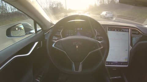 TESLA AUTONOMOUS CAR, MARCH 2018: LENS FLARE: Breakthrough autonomous vehicle navigates and steers itself down freeway on sunny evening. Futuristic driverless Tesla car speeding along sunlit motorway.