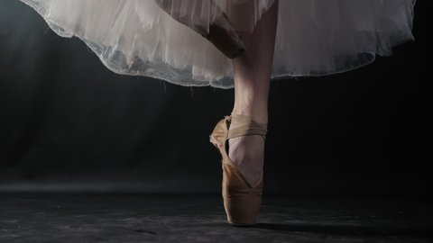 Close up of ballet dancer as she practices exercises on dark stage or studio. Woman's feet in pointe shoes. Ballerina shows classic ballet pas. Slow motion. Flare, gimbal shot.