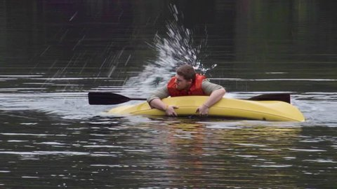 A man struggles in the water with his tipped kayak.