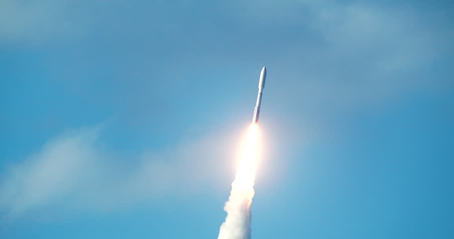 Commercial space rocket flying into sky with bright flames and exhaust smoke. 4K at 120 fps slow motion.