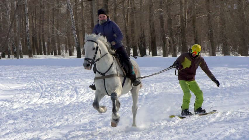 SLOW MOTION : A girl galloping on a horse at a gallop. A horse is dragging a snowboarder guy on a rope. A snowboarder rides on a snowboard in snowdrifts. Girl jockey and guy snowboarder train in pairs