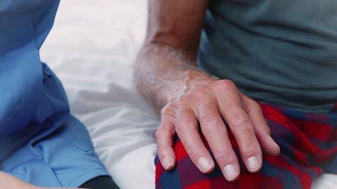 Close Up Of Nurse Comforting Senior Man On Home Visit