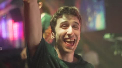Enthusiastic young man fist pumps while partying on a night out at the club.