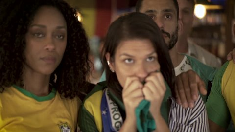 Brazilian football fans looking disappointed while watching televised match in bar