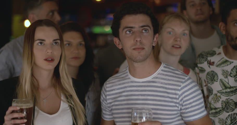 Sports fans cheering while watching televised match in sports bar, slow motion | Shutterstock HD Video #1008892388