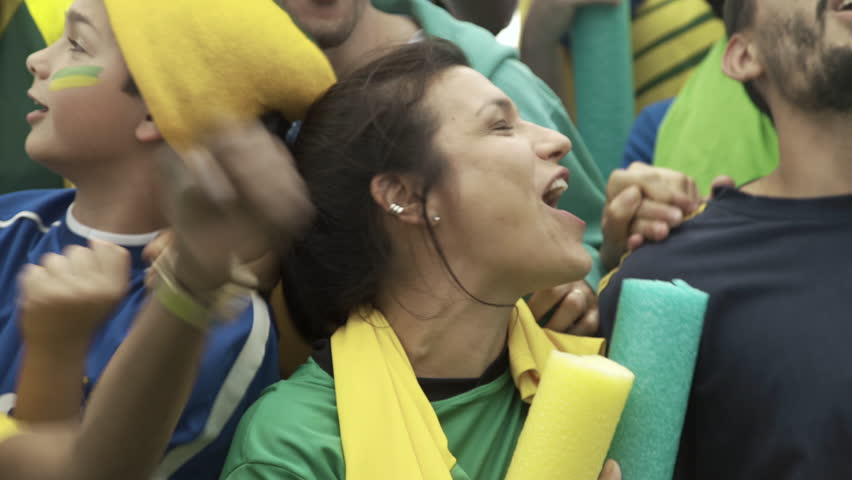 Brazilian soccer fans watching match at stadium and cheering excitedly | Shutterstock HD Video #1008892418