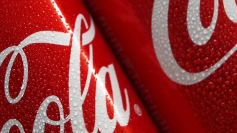 MOSCOW, RUSSIA- CIRCA MARCH 2018: Cold red cans of popular american sort drink with Coca-Cola logo diagonal rotating. Worldwide famous soda cans with drops of water. Front view. Seamless loopable