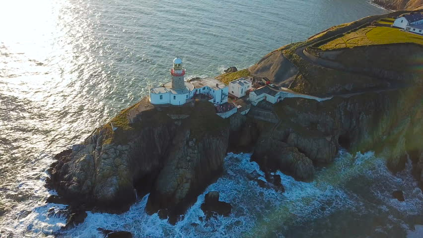 Aerial view of beautiful lighthouse on a cliff in Howth, Ireland | Shutterstock HD Video #1008908348