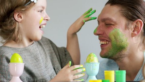 Happy easter. Father and daughter paint each other's eggs and faces. Family jokes