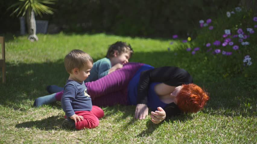 A modern family, millenial parents, and grandmother with two childs playing in a picnic in the garden in a sunny day