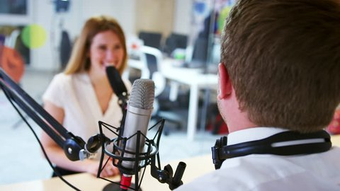 Young man interviewing a guest in a studio for a podcast
