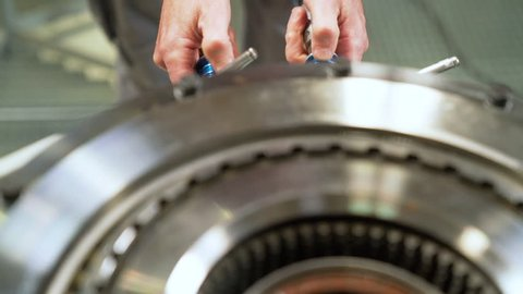 Worker testing gears with high presure machine.