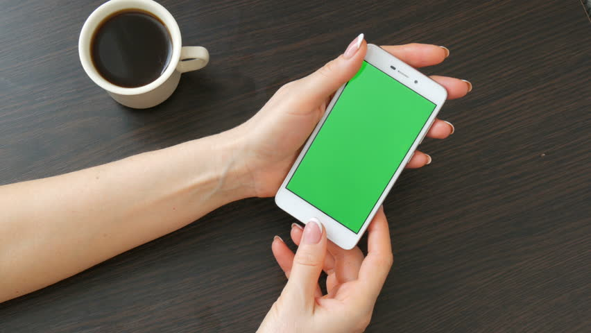 Female hands with beautiful French manicure take white smartphone with Green Screen near white cup of coffee. Using Smartphone,Holding Smartphone with Green Screen on a stylish black wooden table #1008951188