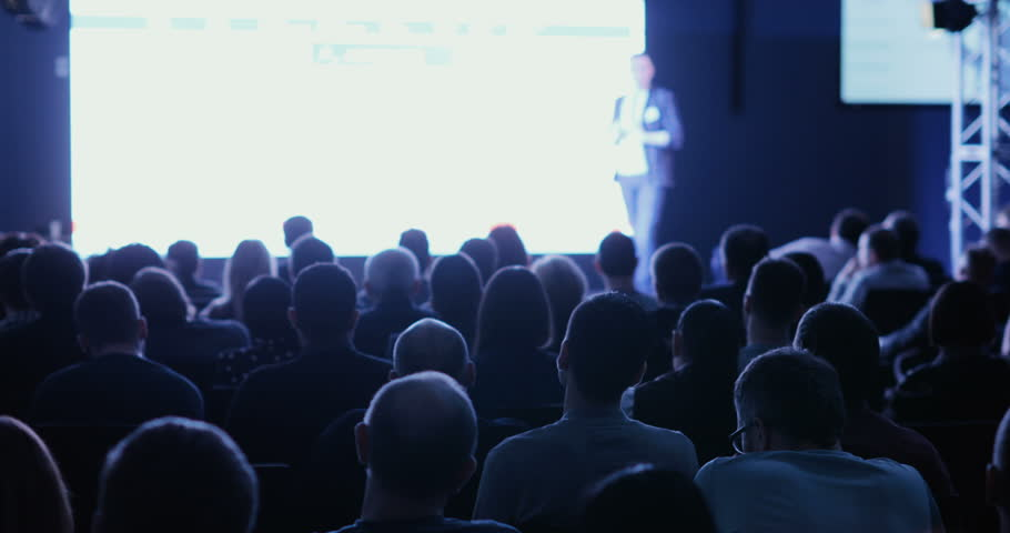 Lecturer tells and shows presentation on projective screen to packed house of listeners | Shutterstock HD Video #1008956918