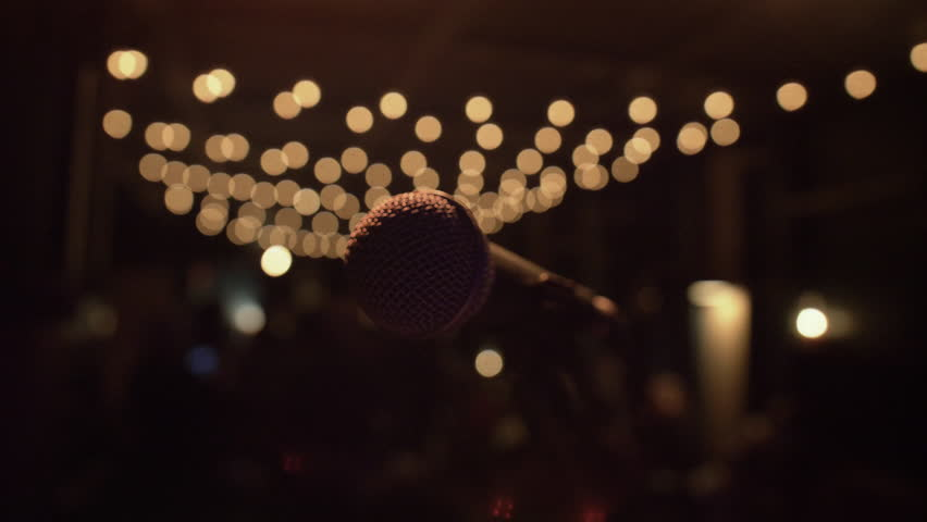 Microphone on a stage with string lights in the background. Intimate, cozy, moody bar location. Cameraes from left to right. Shallow depth of field. 4K Ultra HD. Aspect ratio 1.78:1 (16:9)   Shutterstock HD Video #1008969908