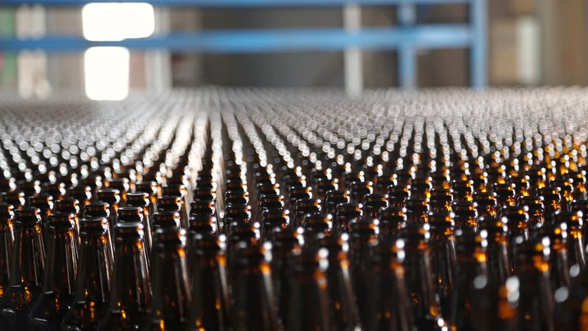 Beer bottle factory. Clean bottles are moving along the conveyor. Preparation of beer bottles for bottling and packaging. Empty brown bottles in a line in factory. Beer bottle production. | Shutterstock HD Video #1008979958