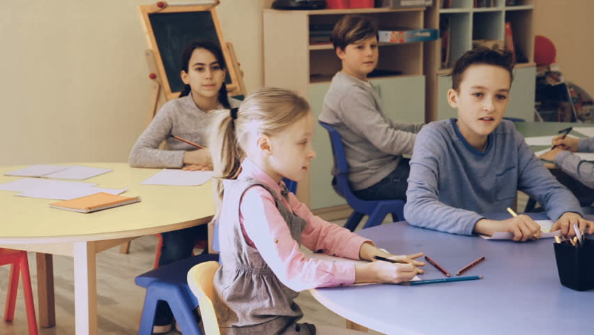 Smiling elementary age children sitting and listening teacher at class  | Shutterstock HD Video #1008984968