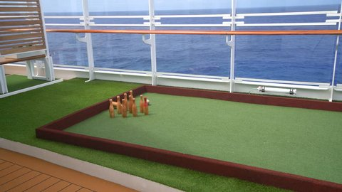 Skittles or ten pin bowling on teak deck of cruise ship with ball coming into view and hitting the pins