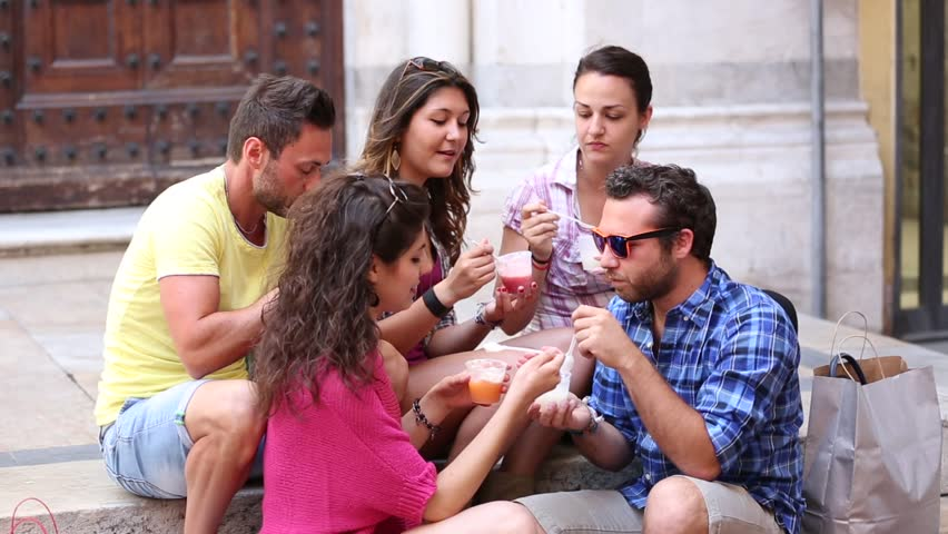 Tourists or friends eating ice cream slush, talking and looking each other. Five persons having fun together on a hot summer day in Pisa, Italy. Women and men sitting on concrete steps and relaxing.