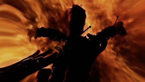 Lens distorted scene: the silhouette of a voodoo doll, pierced by big rusty nails, being cursed by a witch's hand, over a fire pyre.