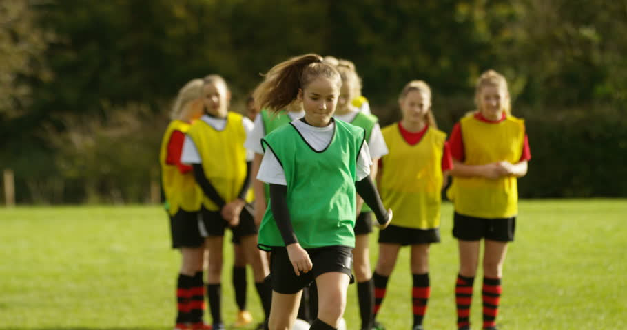 4K Young female soccer team practising ball control & dribbling on school sports field. Slow motion.