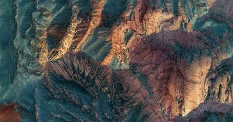 Colorful nature. Aerial view on orange sandstone hills covered with sparse vegetation in Zhangye Danxia National Geopark.