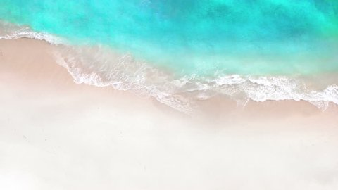 Aerial view of crystal clear sea and white sand beach. Looping Water surface texture, Top view ocean waves slow motion, Sea side white sand, Sun shine  water seamles loop background.