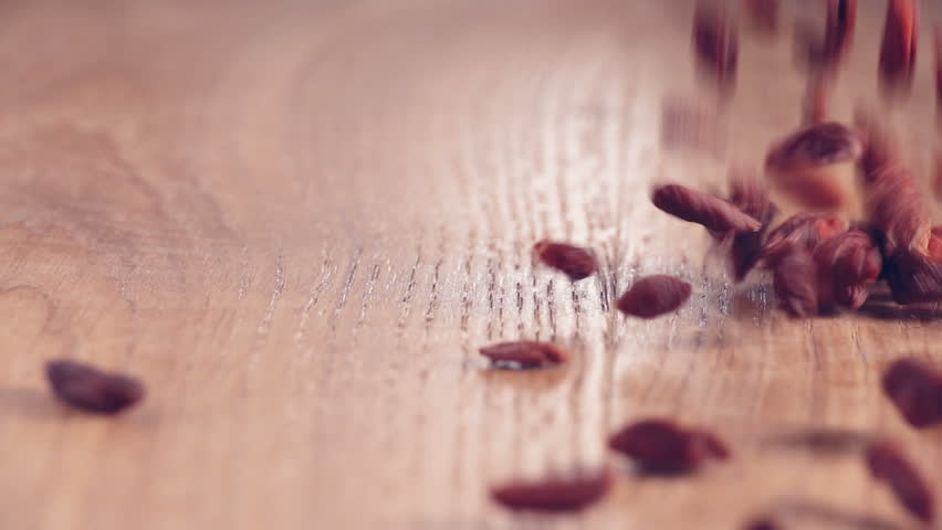 Super food Goji berries poured out equally on wooden table in kitchen. authentic slow motion close up.