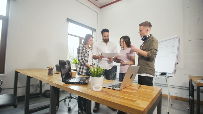 Creative team of students discussing different ideas, standing near brown study desk before the whiteboard, indoor shot in modern educational facilities | Shutterstock HD Video #1009035998