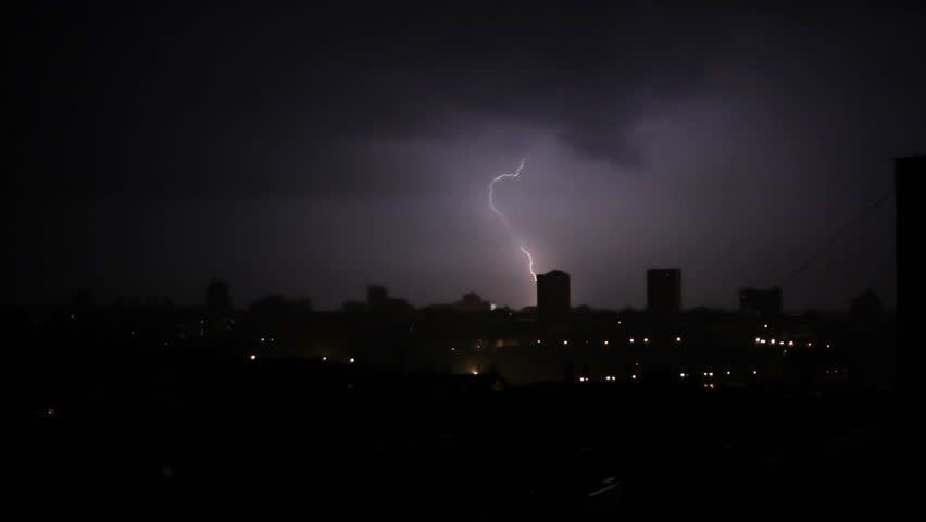 Lightning bolt in the middle of the night during a storm in the city